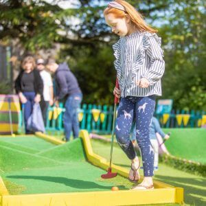 little girl playing crazy golf